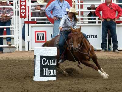A barrel racer sits deep in her saddle during a hard, fast turn