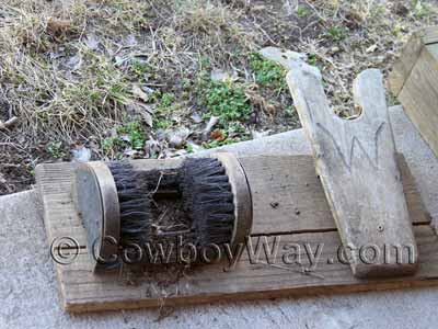 A well-used wooden boot scraper with boot puller and brushes