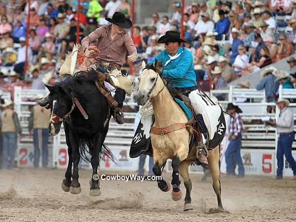 A pickup man closes in on a saddle  bronc rider