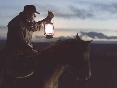 A cowboy on a horse holding a lamp
