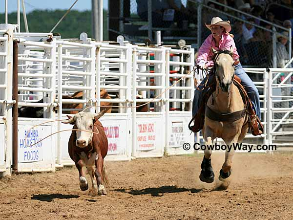A cowgirl ropes a crooked-horned steer
