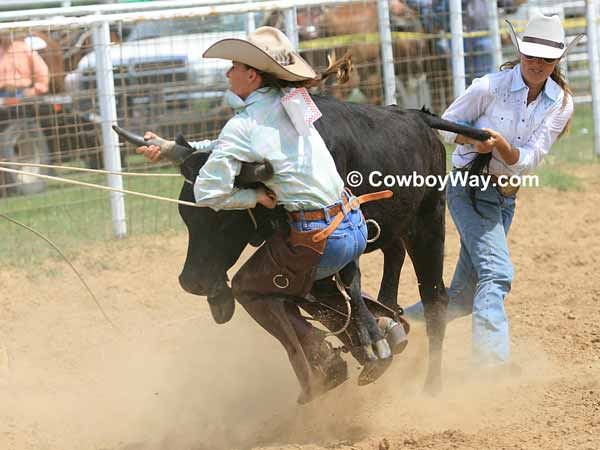 A cowgirl hangs onto a steer even though she is off the ground