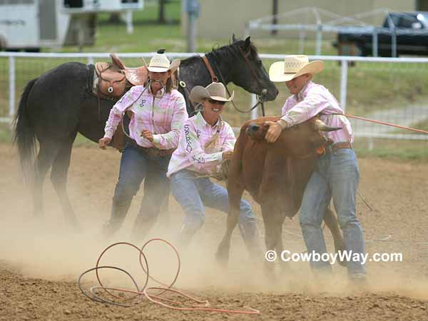 Cowgirls mug their steer in dusty arena