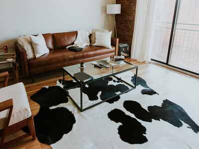 A black and white cowhide rug in a room with moder decor