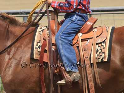 A Dakota roping saddle with a youth rider