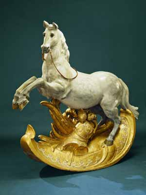 A very old wooden rocking horse with gilded stand