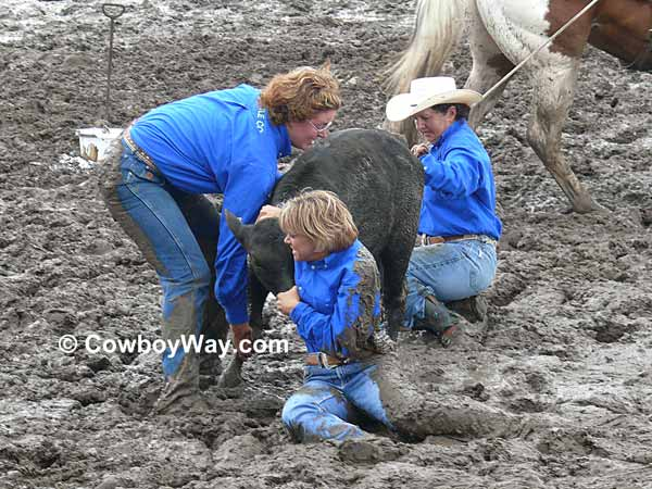Three cowgirls in deep mud with a calf