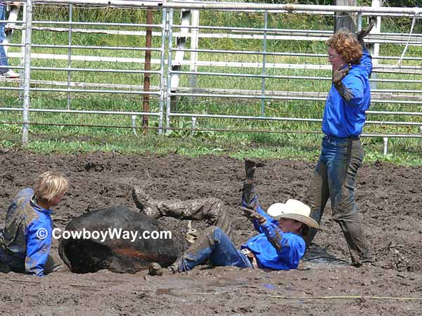 Three cowgirls finish tying their steer