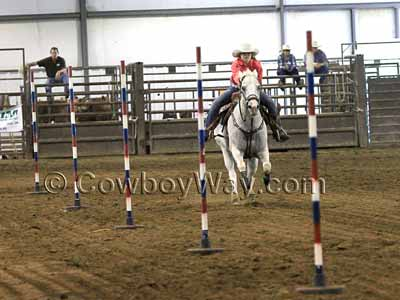 A horse and rider run a pole bending course