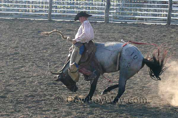 A bronc rider and his ranch saddle go over a bronc's neck