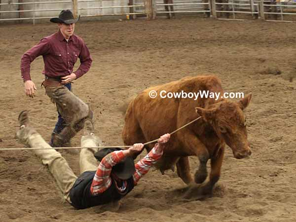 A ranch rodeo contestant hangs onto the rope and gets dragged