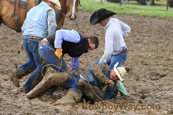 A cowboy covered in mug holds a steer down at a ranch rodeo
