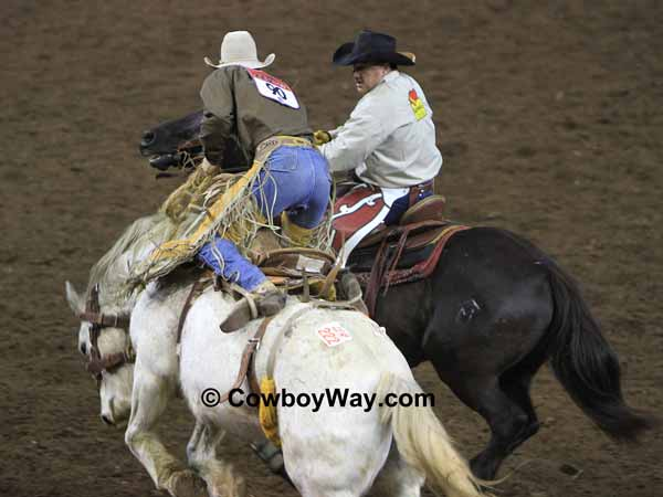 A saddle bronc rider gets off on a pickup man