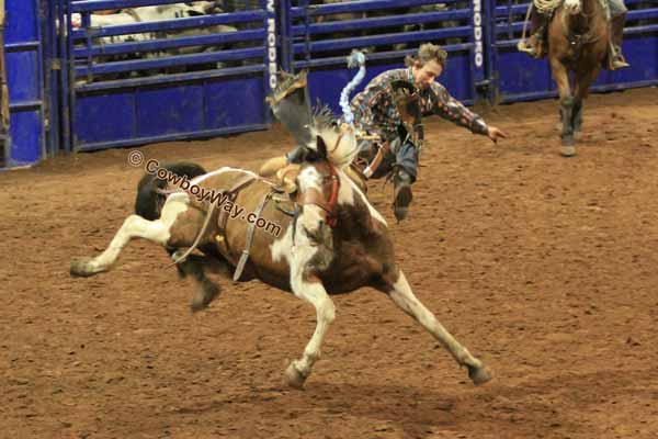 A bronc rider makes a flying dismount off of a saddle bronc