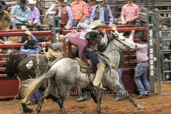 A pickup man helps a saddle bronc rider off his bronc