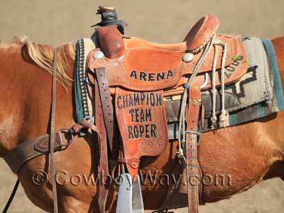 A used trophy roping saddle with lettering
