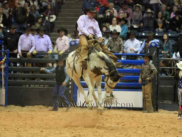 Ryan Wakefield high in the air on a spotted bronc