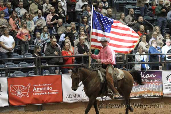 Chris Potter carrying the flag at the WRCA ranch rodeo Finals