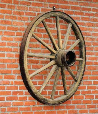 Wooden wagon wheel on a brick wall