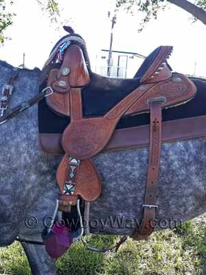 A Tammy Fischer treeless barrel racing saddle on a gray horse