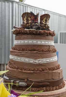 A chocolate wedding cake with cowboy boots for a cake topper